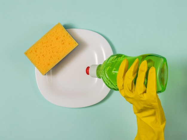 Het aanbrengen van reinigingsmiddel op vuile vaat. huiswerk.
