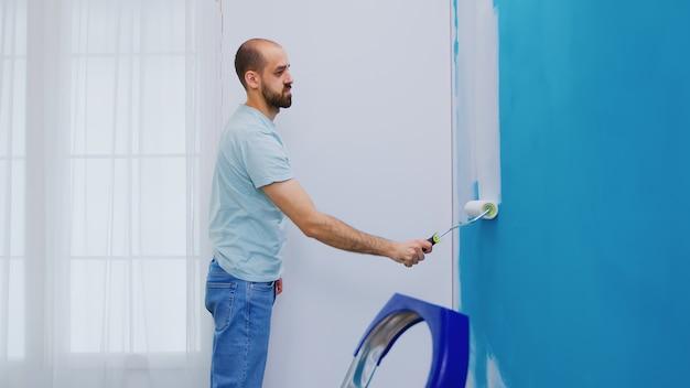 Het aanbrengen van witte verf op de muur tijdens de renovatie van een huis. klusjesman aan het renoveren. appartement herinrichting en woningbouw tijdens renovatie en verbetering. reparatie en decoreren.