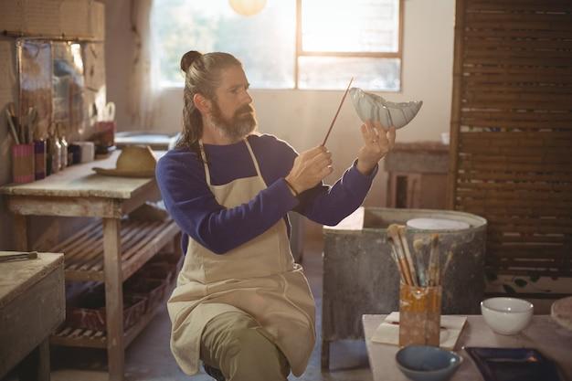 Het aandachtige mannelijke pottenbakker schilderen op kom