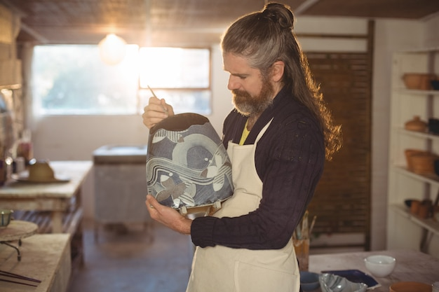 Het aandachtige mannelijke pottenbakker schilderen op pot