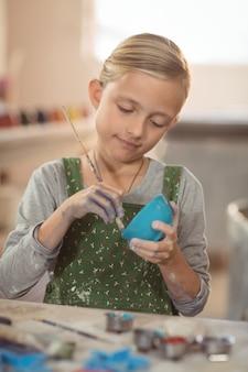 Het aandachtige meisje schilderen op kom