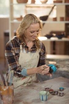 Het aandachtige vrouwelijke pottenbakker schilderen op kom