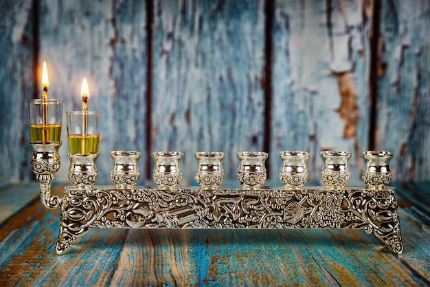 Het aansteken van de eerste kaars op een chanoeka van een brandende chanoeka-kandelaar met kaarsen