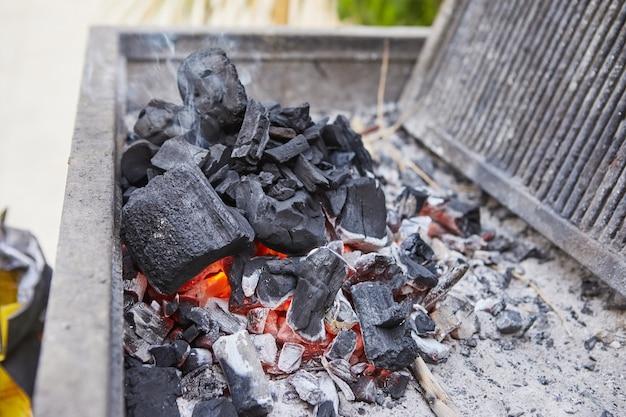 Het aansteken van kolen in de barbecuegrill. bbq-feestje