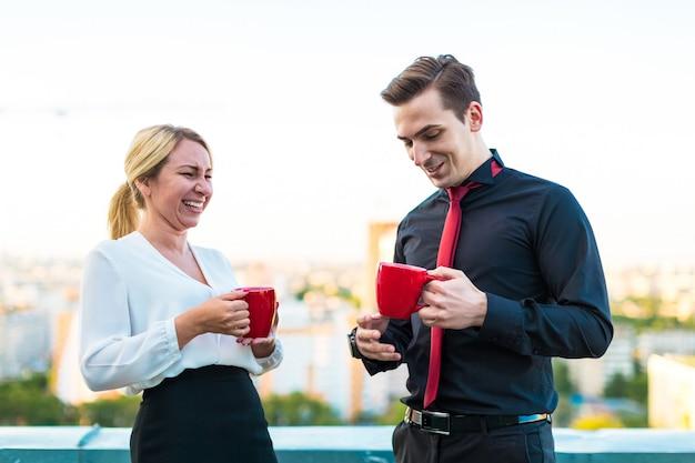 Het aantal zakenlieden, de aantrekkelijke donkerbruine man en de mooie blondevrouw staan op het dak en drinken koffie