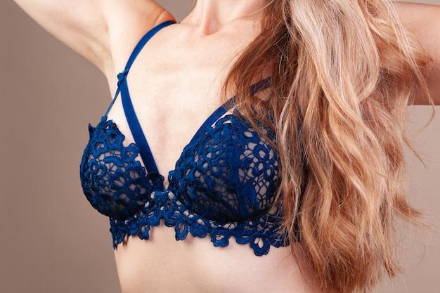Het aantrekkelijke blondevrouw stellen in modieuze lingerie in studio