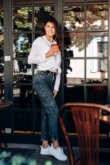 Het aantrekkelijke donkerbruine stellen met een kop van koffie in haar dient een koffie in.
