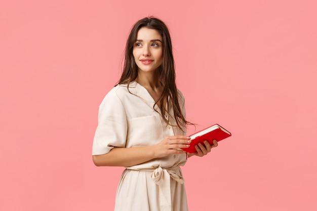Het aantrekkelijke dromerige en romantische leuke meisje in kleding draait zich om kijkend nadenkend, houdend notitieboekje, bereid nota's voor het werk voor, bevindende roze muur, het denken