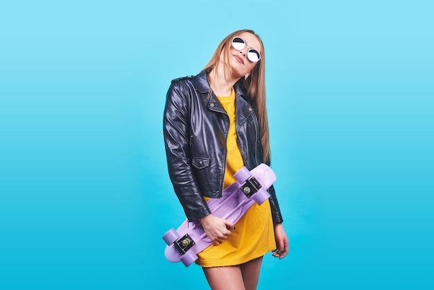 Het aantrekkelijke gelooide meisje met glimlach in gezicht draagt het zwarte leerjasje stellen met plezier