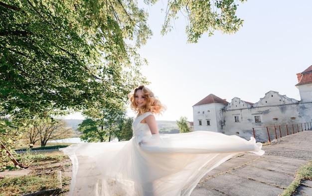 Het aantrekkelijke gelukkige blondemeisje gekleed in witte kleding draait zich om en glimlacht op de zonnige dag dichtbij oud steenkasteel