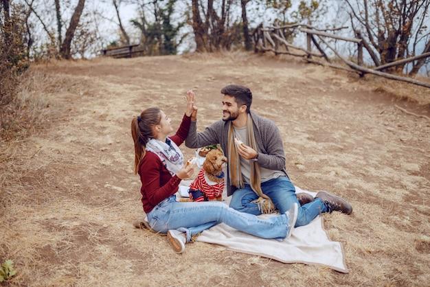 Het aantrekkelijke glimlachende multiculturele paar kleedde toevallige zitting op deken bij picknick, etend sandwiches en het geven van high five. herfstseizoen.