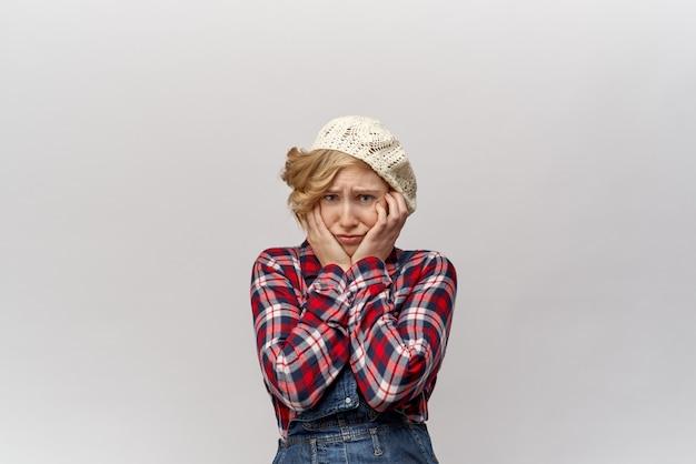 Het aantrekkelijke jonge blonde studentenmeisje in ouderwetse kleren in retro stijl zoals een hillbilly in verwarring grijpt haar gezicht in handen met verstoorde geschokte uitdrukking.