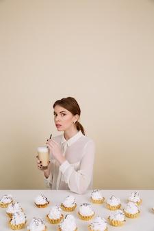 Het aantrekkelijke jonge dame stellen dichtbij cupcakes die koffie houden