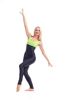 Het aantrekkelijke jonge de instructeur van de blonde vrouwelijke aerobics stellen op witte achtergrond.