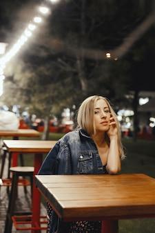 Het aantrekkelijke jonge kaukasische blondemeisje zit in openlucht dichtbij de lijst