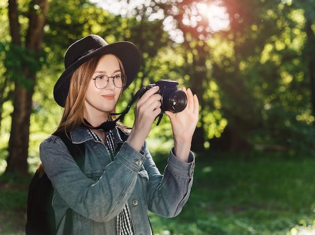 Het aantrekkelijke jonge meisje in een hoed maakt in openlucht foto op camera