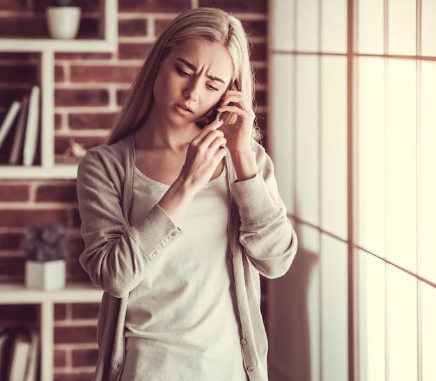 Het aantrekkelijke jonge meisje spreekt op de mobiele telefoon.