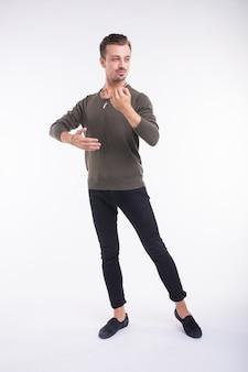 Het aantrekkelijke jonge mens dansen, die pret op witte achtergrond heeft. stijlvolle vooruitzichten.
