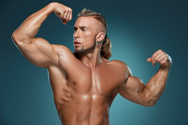 Het aantrekkelijke mannelijke lichaamsbouwer stellen