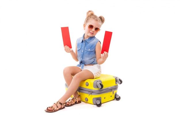 Het aantrekkelijke meisje in blauw overhemd, witte borrels en zonnebril zit op de gele koffer