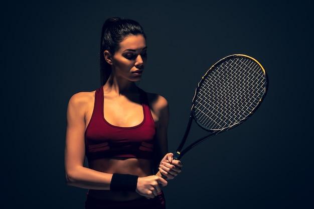 Het aantrekkelijke meisje in sportkleding houdt een tennisracket vast