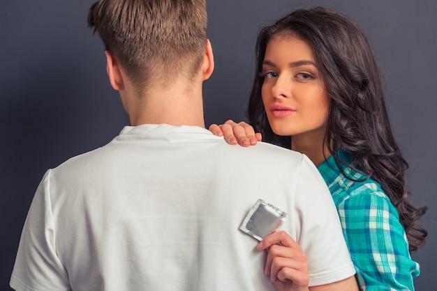 Het aantrekkelijke meisje toont een condoom en bekijkt camera.