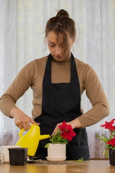 Het aantrekkelijke positieve blije meisje die petuniabloem water geven met kan na het planten