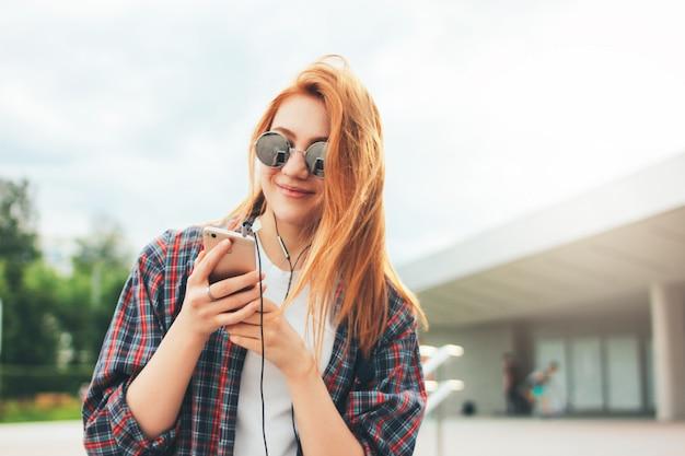 Het aantrekkelijke roodharige glimlachende meisje in ronde zonnebril met telefoon dient binnen vrijetijdskleding het luisteren muziek in