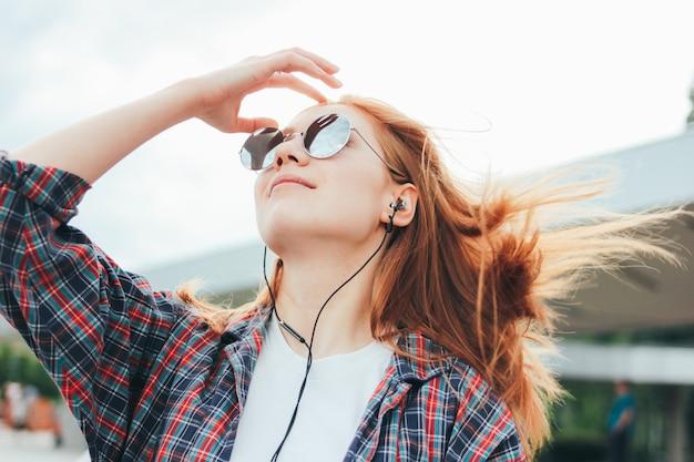 Het aantrekkelijke roodharige glimlachende meisje in ronde zonnebril met telefoon in haar dient vrijetijdskleding in
