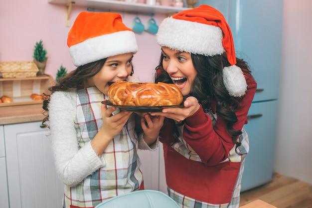 Het aardige en positieve jonge vrouw en meisje houden plaat met pastei en bekijken elkaar. ze bijten het. vrouw en meisje glimlachen. ze dragen schorten en kerstmutsen.