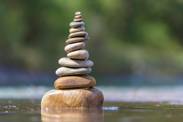 Het abstracte beeld van de close-up van natte ruwe natuurlijke bruine ongelijke verschillende grootte en vormt stenen evenwichtig zoals het oriëntatiepunt van de piramidestapel in ondiep water op vage blauwgroene nevelig.