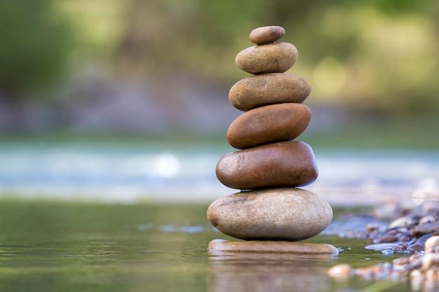 Het abstracte beeld van de close-up van natte ruwe natuurlijke bruine ongelijke verschillende grootte en vormt stenen evenwichtig zoals het oriëntatiepunt van de piramidestapel in ondiep water op vage blauwgroene nevelige exemplaar ruimtescène.