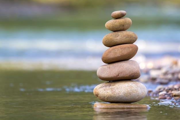 Het abstracte beeld van de close-up van natte ruwe natuurlijke bruine ongelijke verschillende grootte en vormt stenen evenwichtig zoals het oriëntatiepunt van de piramidestapel in ondiep water