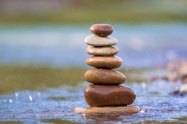 Het abstracte beeld van de close-up van natte ruwe natuurlijke bruine ongelijke verschillende grootte en vormt stenen