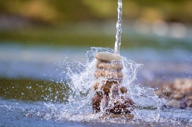 Het abstracte beeld van de close-up van water dat neer op ruwe natuurlijke bruine ongelijke verschillende grootte en vormenstenen giet evenwichtig zoals piramide stapeloriëntatiepunt op vage blauwgroene nevelig
