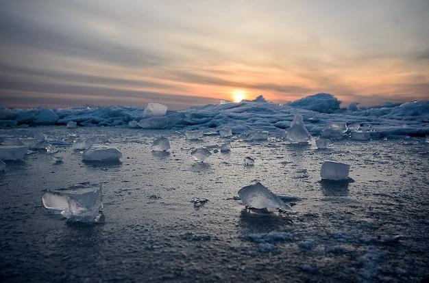 Het abstracte bevroren zeegezicht van de de winterzonsopgang met ijs en kleurde de hemel.