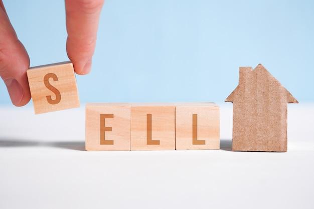Het abstracte huis dat van kartonhand wordt gemaakt houdt met houten kubussen met het woord verkoopt. home verkoop.