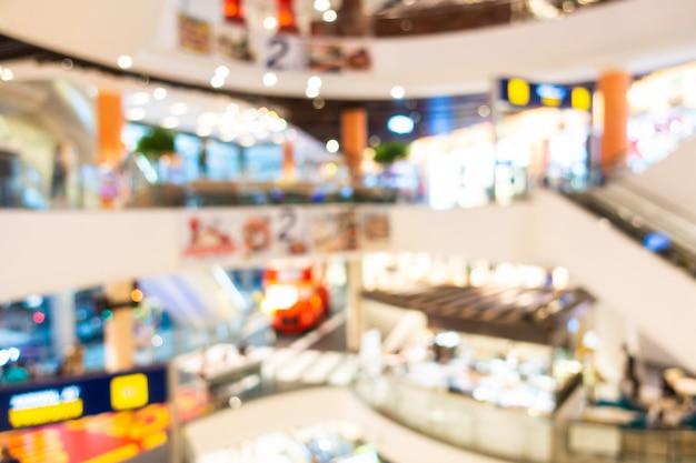 Het abstracte onduidelijke beeld en defocused winkelcomplex en kleinhandelsbinnenland van warenhuis, vage fotoachtergrond