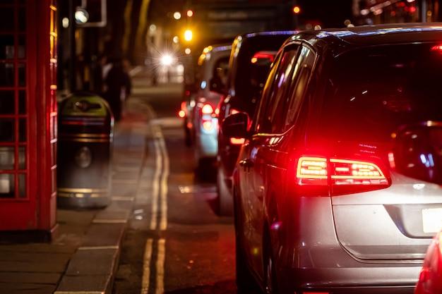 Het achteraanzicht op de file op de straat in het centrum 's nachts, close-up