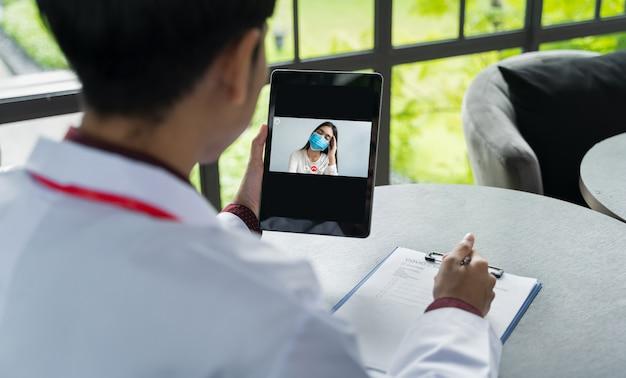 Het achteraanzicht van de arts communiceert met de patiënt en draagt een masker via tabletten.