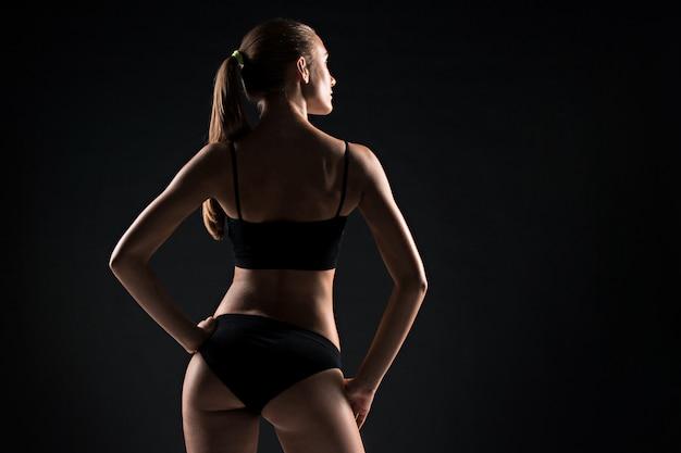 Het achteraanzicht van gespierde jonge vrouw atleet poseren op grijs