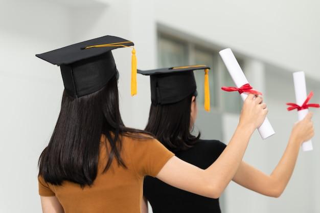 Het achterbeeld van een vrouwelijke studentafgestudeerden die een zwarte hoeden gele leeswijzer dragen