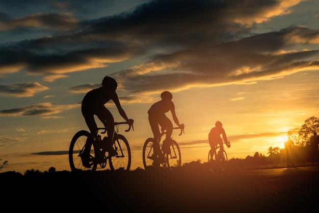 Het achtereind van fietsers berijdt fiets op de achtergrond van de zonsondergangtijd