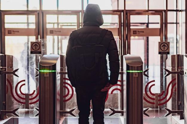 Het achterportret van persoon gaat door veiligheidsturnstile door