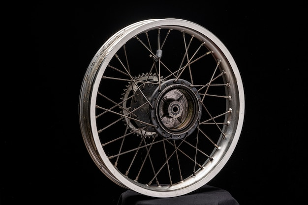 Het achterwiel van een motorfiets zonder band, oud gebruikt. close-up zwarte ruimte