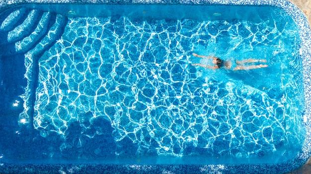 Het actieve meisje in mening van de zwembad de luchthommel van hierboven, jonge vrouw zwemt in blauw water, tropische vakantie, vakantie bij het toevluchtconcept