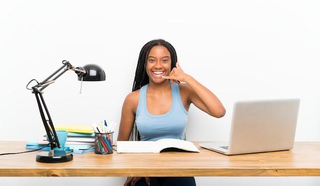 Het afrikaanse amerikaanse meisje die van de tienerstudent met lang gevlecht haar in haar werkplaats telefoongebaar maken. bel me terug teken