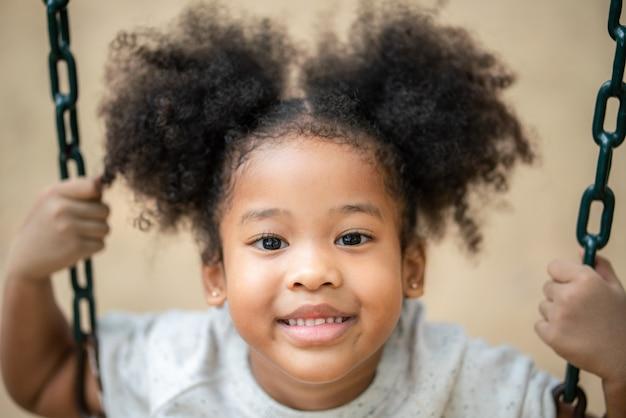 Het afrikaanse amerikaanse meisje glimlachen bekijkt camera bij speelplaats in het park