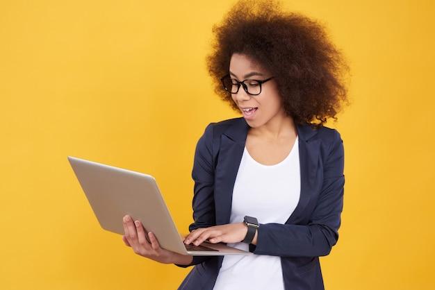 Het afrikaanse amerikaanse meisje in kostuum stelt met geïsoleerd laptop.