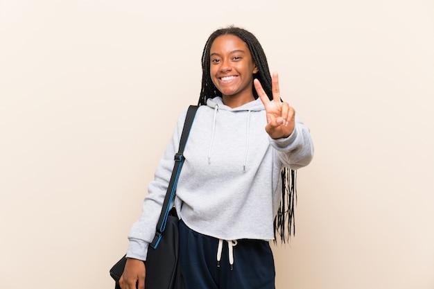 Het afrikaanse amerikaanse meisje van de sporttiener met lang gevlecht haar die en overwinningsteken glimlachen tonen